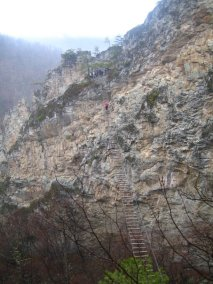 "November 22. Via Ferrata. I am the speck in the pink raincoat in the middle of the bridge of death. Unfortunately this Via Ferrata has changed hands and become super expensive, but I'll never forget the way our group challenged ourselves to climb that course and how we all succeeded and celebrated together. Via Ferrata means ""iron way,"" and this course is literally a series of rungs and rope bridges winding around a mountain in Nelson Rocks, WV. How come every time I do something terrifying, I am in West Virginia?"